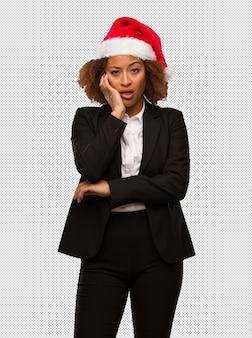 Jeune femme noire portant un bonnet de noel fatigué et très fatigué