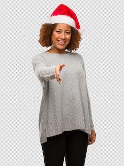 Jeune femme noire portant un bonnet de noel tendre la main pour saluer quelqu'un