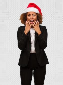 Jeune femme noire portant un bonnet de noël très effrayé et effrayé