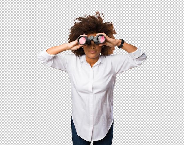 Jeune femme noire regardant à travers les jumelles