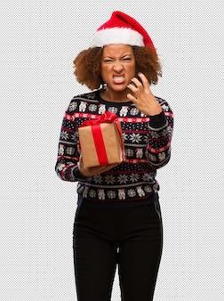 Jeune femme noire tenant un cadeau au jour de noël en colère et contrariée