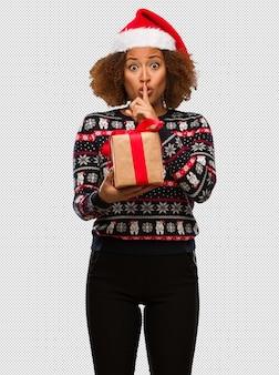 Jeune femme noire tenant un cadeau au jour de noël, gardant un secret ou demandant le silence