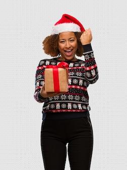 Jeune femme noire tenant un cadeau au jour de noël surpris et choqué