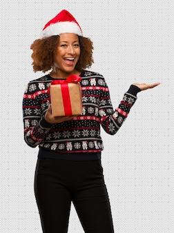Jeune femme noire tenant un cadeau au jour de noël tenant quelque chose avec la main