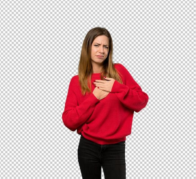 Jeune femme avec un pull rouge ayant une douleur au coeur