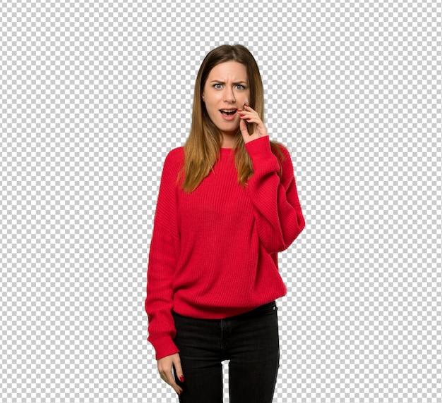 Jeune femme avec un pull rouge avec une expression faciale surprise et choquée