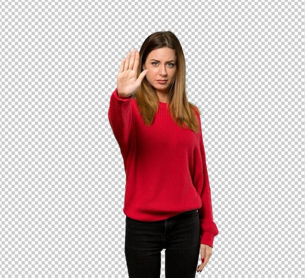 Jeune femme avec un pull rouge faisant un geste d'arrêt refusant une situation qui pense mal