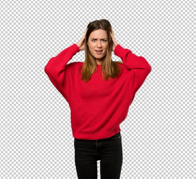 Jeune femme avec un pull rouge frustré et prend les mains sur la tête