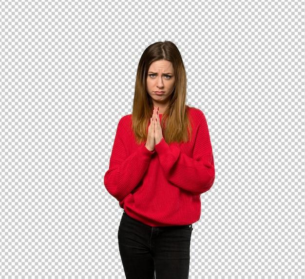 Jeune femme avec un pull rouge garde la paume ensemble. personne demande quelque chose