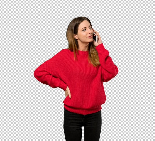 Jeune femme, à, pull rouge, garder conversation, à, les, téléphone portable