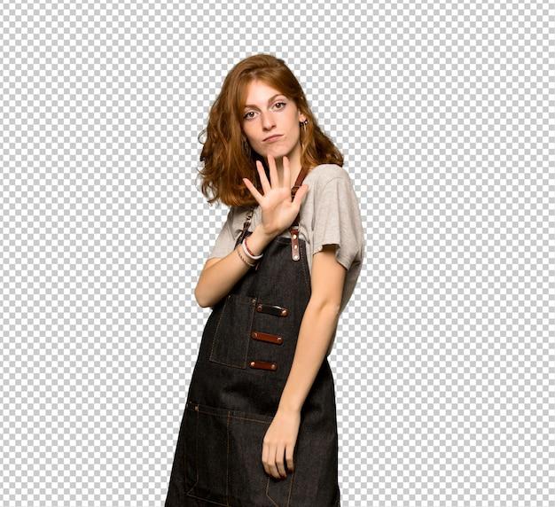 Jeune femme rousse avec un tablier comptant cinq avec les doigts