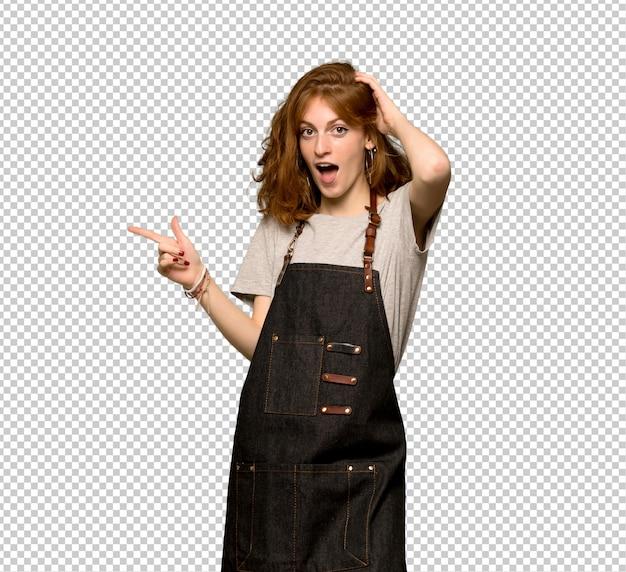 Jeune femme rousse avec un tablier pointant le doigt sur le côté et présentant un produit