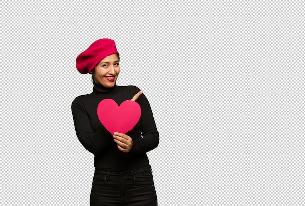 Jeune femme en saint valentin souriant et pointant sur le côté