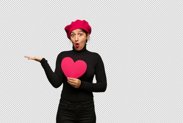 Jeune femme en saint valentin tenant quelque chose sur la main de la paume