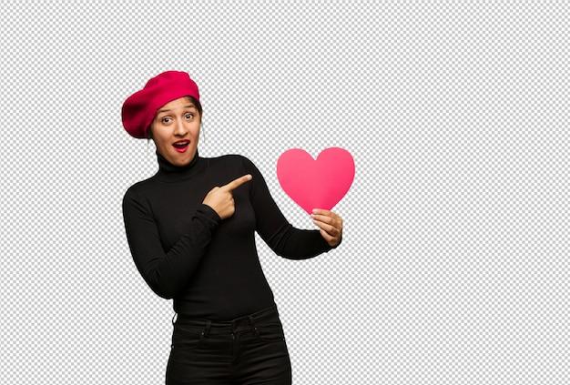 Jeune femme en saint valentin tenant quelque chose avec la main