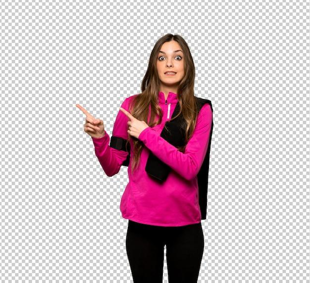 Jeune femme sportive effrayée et pointant sur le côté