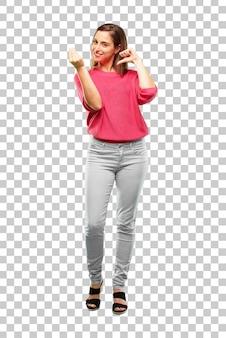 Jeune femme tout le corps. avoir l'air heureux, fier et satisfait, faire des gestes d'argent ou d'argent