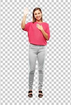 Jeune femme tout le corps. souriant avec assurance tout en faisant une promesse ou un serment sincère