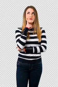 Jeune fille blonde ayant des doutes et avec une expression de visage confuse