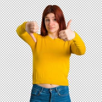 Jeune fille rousse avec un pull jaune faisant du bon signe. personne indécise entre oui ou non