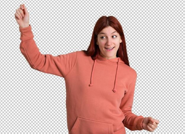 Jeune fille rousse avec un sweat-shirt rose aime danser tout en écoutant de la musique lors d'une fête