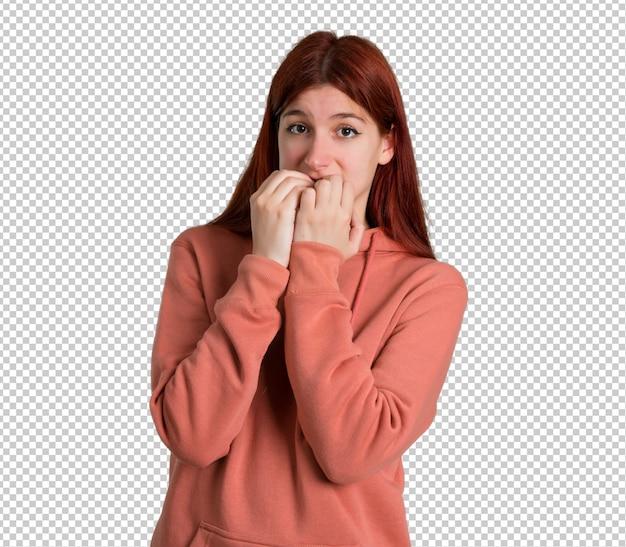 Jeune fille rousse avec un sweat-shirt rose est un peu nerveux et effrayé de mettre les mains à la bouche