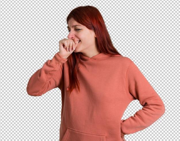 Jeune fille rousse avec un sweat-shirt rose souffre de toux et se sent mal