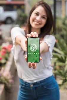 Jeune fille tenant une maquette de smartphone avec concept de jardinage