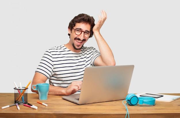 Jeune graphiste barbu avec un ordinateur portable heureux de réaliser de bonnes et surprenantes nouvelles
