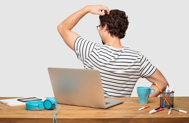 Jeune graphiste barbu avec vue arrière d'un ordinateur portable, main sur la hanche et tête de grattage