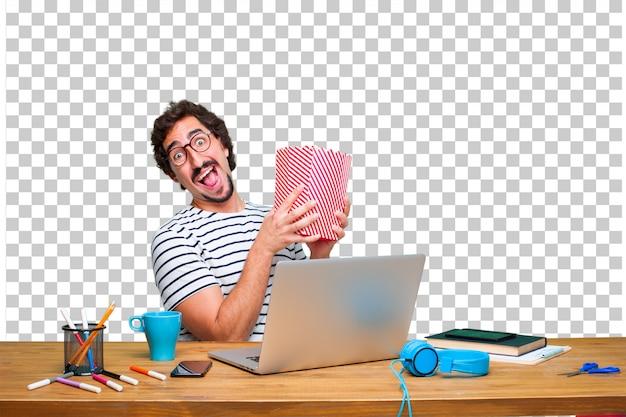 Jeune graphiste folle sur un bureau avec un ordinateur portable et un seau de maïs soufflé