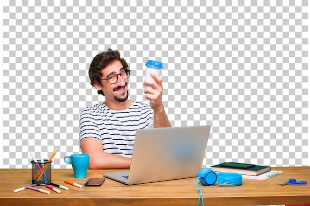 Jeune graphiste fou sur un bureau avec un ordinateur portable et un café à emporter