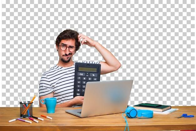 Jeune graphiste fou sur un bureau avec un ordinateur portable et une calculatrice