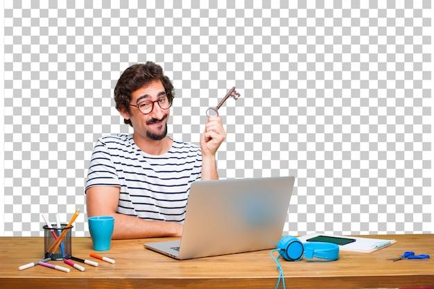 Jeune graphiste fou sur un bureau avec un ordinateur portable et une clé vintage