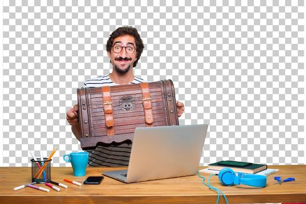 Jeune graphiste fou sur un bureau avec un ordinateur portable et un coffre de pirate