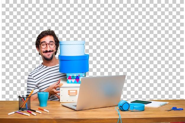 Jeune graphiste fou sur un bureau avec un ordinateur portable et avec le concept de boîte cadeau