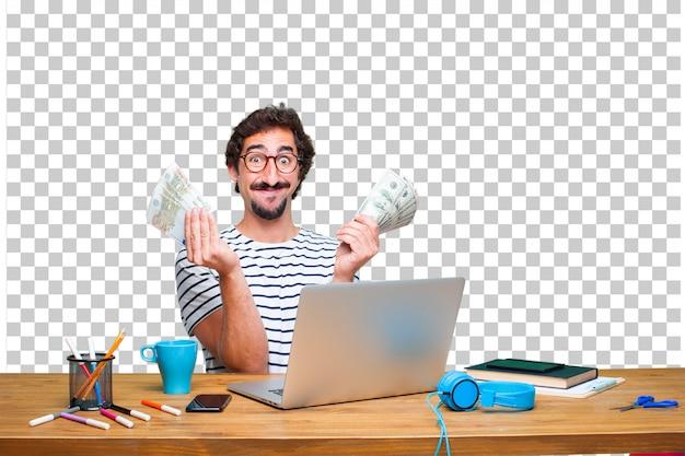 Jeune graphiste fou sur un bureau avec un ordinateur portable et concept de paiement, d'achat ou d'argent