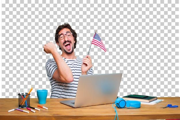 Jeune graphiste fou sur un bureau avec un ordinateur portable et un drapeau américain