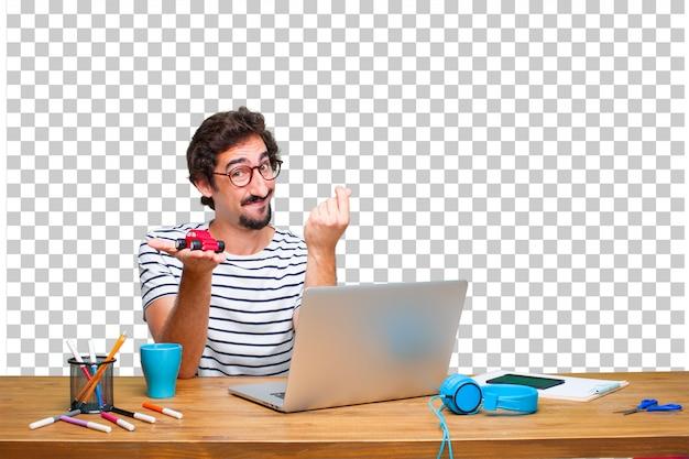 Jeune graphiste fou sur un bureau avec un ordinateur portable et un modèle de voiture rouge