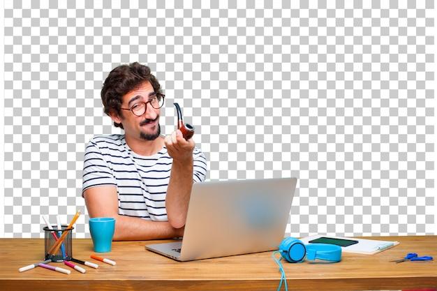 Jeune graphiste fou sur un bureau avec un ordinateur portable et une pipe vintage fumée