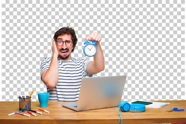 Jeune graphiste fou sur un bureau avec un ordinateur portable et un réveil