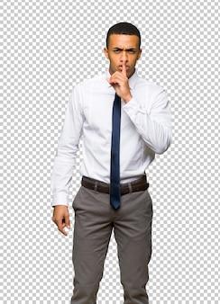 Jeune homme d'affaires américain afro montrant un signe de silence geste mettant le doigt dans la bouche