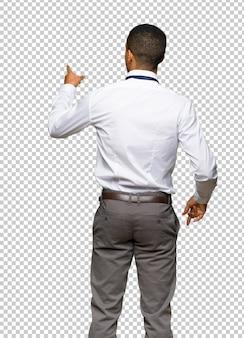Jeune homme d'affaires américain afro, pointant vers l'arrière avec l'index