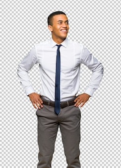 Jeune homme d'affaires américain afro posant avec les bras à la hanche et en riant