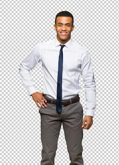 Jeune homme d'affaires américain afro posant avec les bras à la hanche et souriant