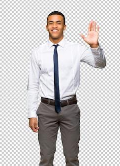 Jeune homme d'affaires américain afro saluant avec la main avec une expression heureuse
