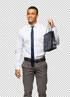 Jeune homme d'affaires américain afro tenant beaucoup de sacs à provisions