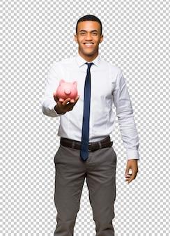 Jeune homme d'affaires américain afro tenant une tirelire