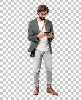 Jeune homme d'affaires barbu portant un blazer à l'aide d'un téléphone intelligent