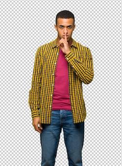 Jeune homme afro américain montrant un geste du silence mettant le doigt dans la bouche